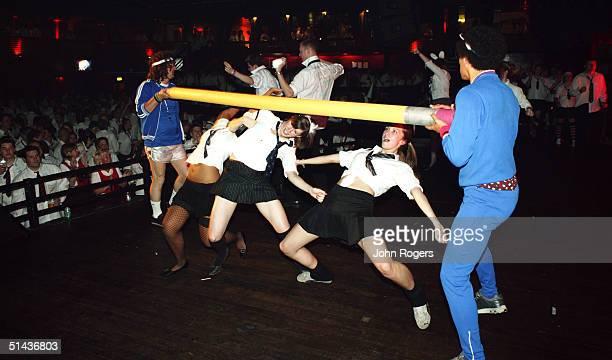 Revellers limbo dance under a pole during a SchoolDiscocom club night at London's Hammersmith Palais nightclub on July 3 2004 in London Attendees...