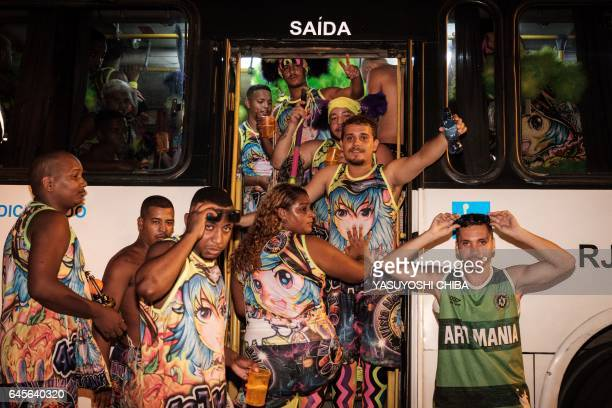 Revellers of batebola street carnival band perform get into a chartered bus to move to other areas of the city on the first day of carnival in Rio de...