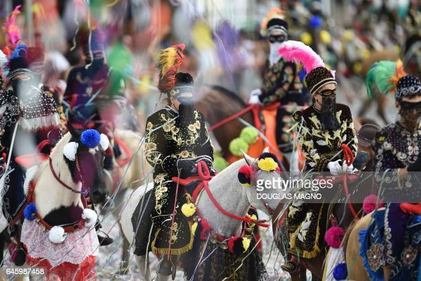 Revellers participate in the traditional carnival on horseback in Bonfim Minas Gerais state southeastern Brazil on February 27 2017 Dressed in...