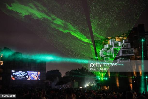 Revellers party and watch a DJ in Block 9 in the Shangri La area as politcal satire messages appear on a wall at Glastonbury Festival Site on June 24...