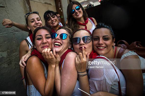 Revellers pose for a picture as they enjoy the atmosphere during the opening day or 'Chupinazo' of the San Fermin Running of the Bulls fiesta on July...