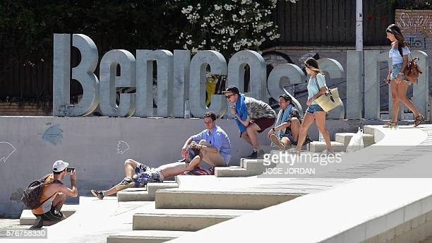 Revellers pose in front of a sculpture reading the name of the city of Benicassim during the fourth and last day of the 2016 Benicassim International...