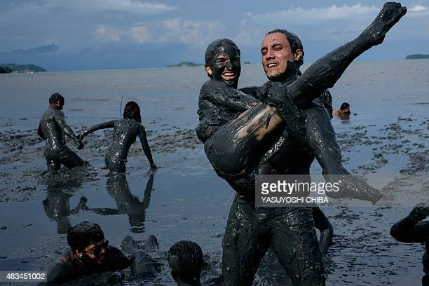 Revellers prepare for 'Bloco da Lama' a mud carnival in Paraty about 250km south of Rio de Janeiro Brazil on February 14 2015 'Bloco da Lama' was...