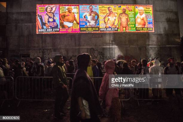 Revellers queue underneath a politcal sign mocking world politicians to enter a club in Block 9 in the Shangri La area at Glastonbury Festival Site...