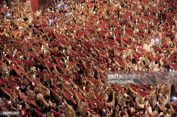 Revellers raise red scarves and candles as they sing the song 'Pobre de Mi' marking the end of the San Fermin festival in Pamplona Spain early on...