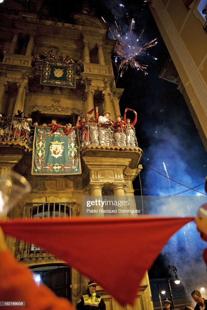 Revellers raise their scarves and candles as they sing the 'Pobre de Mi' song, marking the end of the San Fermin festival on July 15, 2014 in Pamplona, Spain. The annual Fiesta de San Fermin, made famous by the 1926 novel 'The Sun Also Rises' by U.S. author Ernest Hemingway, involves the running of the bulls through the historic heart of Pamplona.