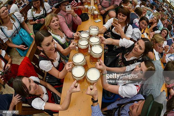 Revellers raise their steins of beer for a toast at the Hofbraeu tent on the opening day of the 2015 Oktoberfest on September 19 2015 in Munich...