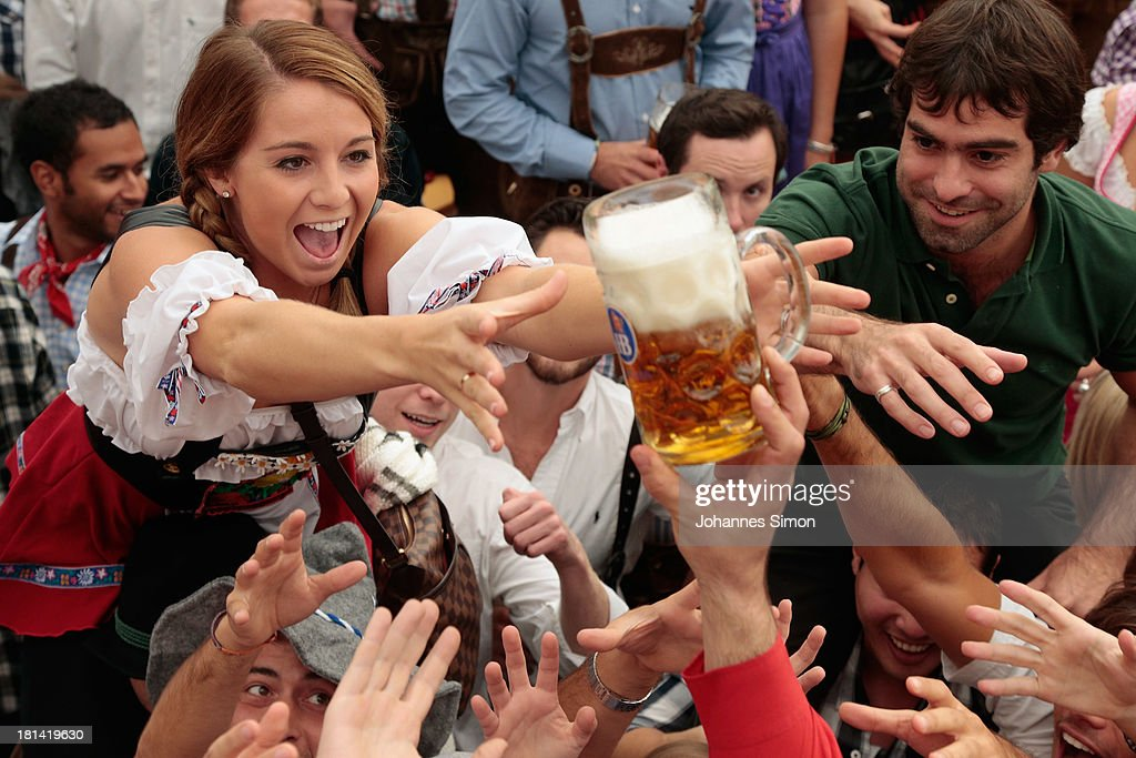 Revellers reach for the first beer mug at Hofbraeuhaus beer tentduring day 1 of the Oktoberfest 2013 beer festival at Theresienwiese on September 21...
