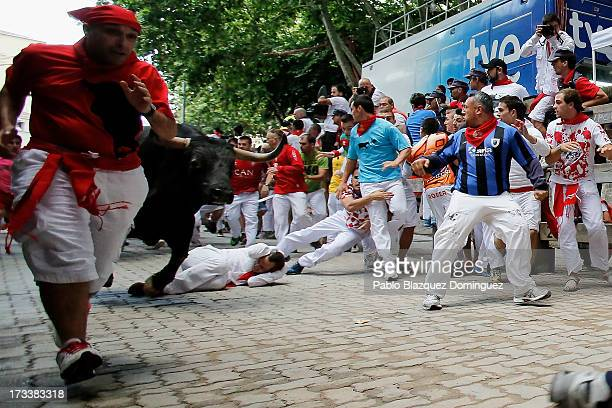 Revellers run with a Fuente Ymbro's fighting bull entering the bullring during the eighth day of the San Fermin Running Of The Bulls festival on July...