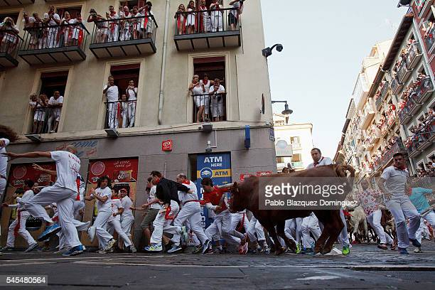 Revellers run with Cebada Gago's fighting bulls entering Estafeta Street during the third day of the San Fermin Running of the Bulls festival on July...