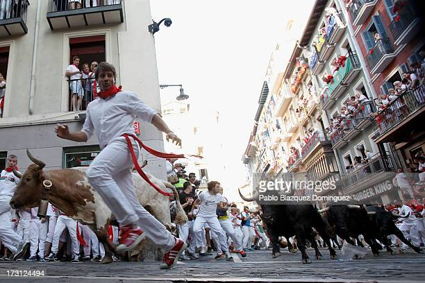 Revellers run with Dolores Aguirre's ranch fighting bulls at Curva Estafeta during the third day of the San Fermin Running Of The Bulls festival on...