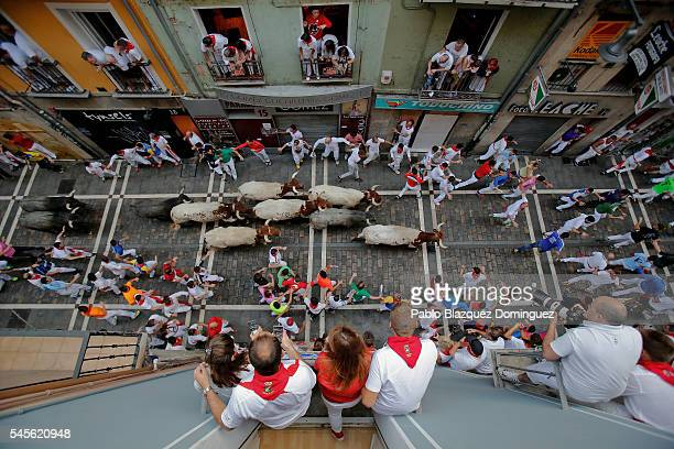 Revellers run with Jose Escolar Gil's fighting bulls along Estafeta Street during the fourth day of the San Fermin Running of the Bulls festival on...