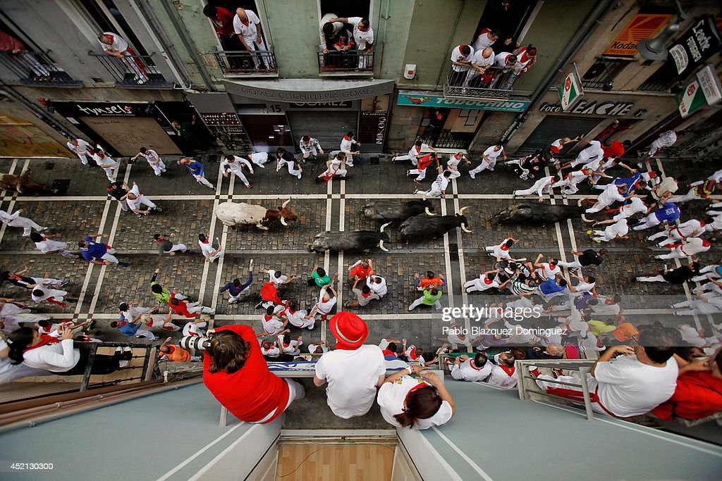 Revellers run with Miura's fighting bulls at Calle Estafeta as people look over from balconies during the ninth day of the San Fermin Running Of The Bulls festival on July 14, 2014 in Pamplona, Spain. The annual Fiesta de San Fermin, made famous by the 1926 novel of US writer Ernest Hemingway 'The Sun Also Rises', involves the running of the bulls through the historic heart of Pamplona.