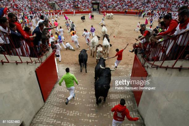 Revellers run with Puerto de San Lorenzo's fighting bulls entering the bullring during the fourth day of the San Fermin Running of the Bulls festival...