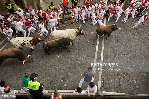 Revellers run with the Fuente Ymbro fighting bulls along Consistorial Square during the fifth day of the San Fermin Running of the Bulls festival on...