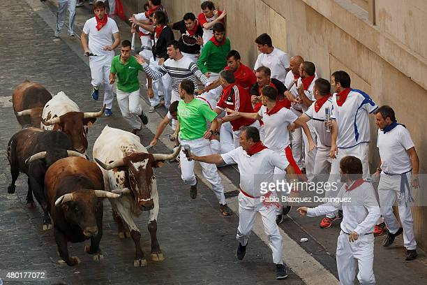 Revellers run with the Fuente Ymbro fighting bulls along Santo Domingo Street during the fifth day of the San Fermin Running of the Bulls festival on...