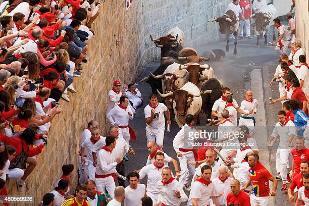 Revellers run with the Garcigrande's fighting bulls along Santo Domingo Street during the eighth day of the San Fermin Running Of The Bulls festival...