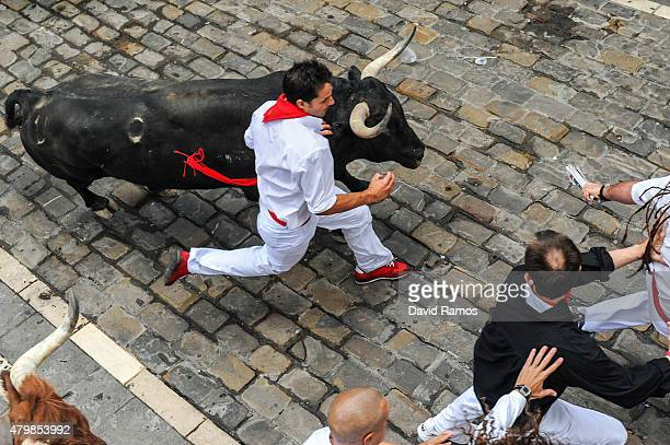 Revellers run with the Tajo and the Reina's fighting bulls entering Estafeta street during the third day of the San Fermin Running of the Bulls...