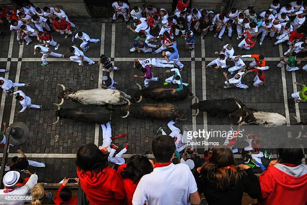Revellers run with the Victoriano del Rio Cortes' fighting bulls along Estafeta street during the fourth day of the San Fermin Running of the Bulls...