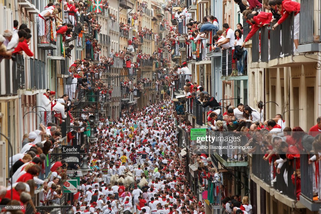 Revellers run with Torrestrella's fighting bulls along the Calle Estafeta during the second day of the San Fermin Running Of The Bulls festival on July 7, 2014 in Pamplona, Spain. The annual Fiesta de San Fermin, made famous by the 1926 novel of US writer Ernest Hemingway 'The Sun Also Rises', involves the running of the bulls through the historic heart of Pamplona.