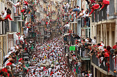 Revellers run with Torrestrella's fighting bulls along the Calle Estafeta during the second day of the San Fermin Running Of The Bulls festival on...