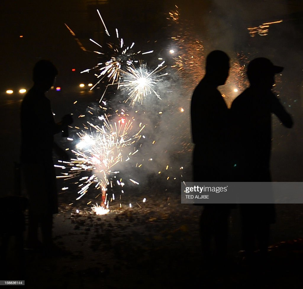 Revellers set off firecrackers as they usher New Year in Manila on January 1, 2013. Philippine officials on December 31, reported more injuries from fireworks as the emergency services braced for a night of thunderous and sometimes deadly merrymaking to usher in the new year.