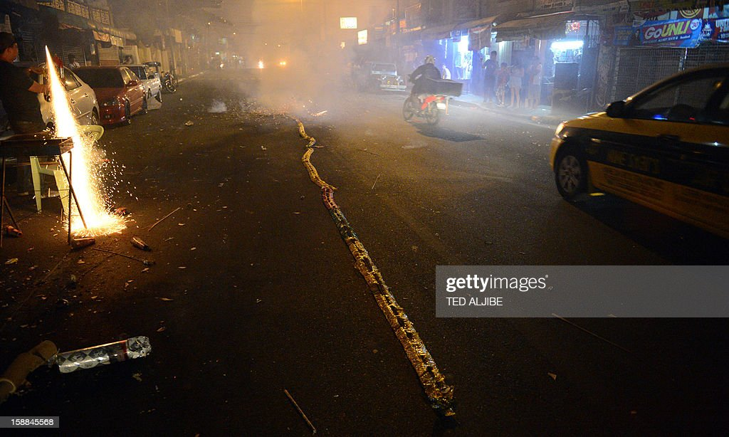 Revellers set off firecrackers to usher in New Year's Day as motorists maneuver around to avoid the festivities in Manila early on January 1, 2013. In the capital Manila, authorities had been bracing for the annual rush of injuries as families celebrated with do-it-yourself firework displays and shot celebratory bullets into the air.