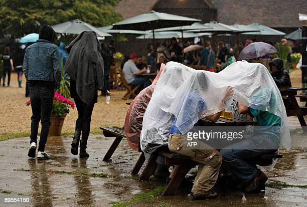 Revellers shelter from the rain at the Sonisphere rock festival at Knebworth on August 1 2009 The festival runs over two days and is set to features...