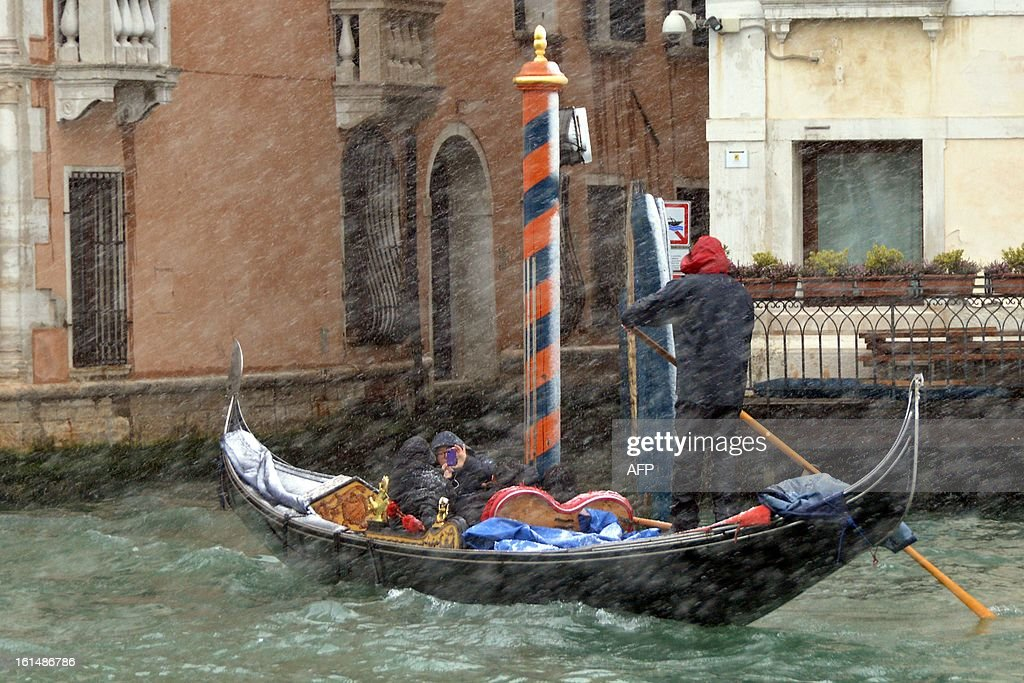 Revellers sit in a gondola under with snow during the carnival on February 11, 2013 in Venice. The 2013 edition of the Venice carnival is untitled ' Live in Colour' and runs from January 26 to February 12.