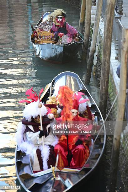 Revellers sit in gondolas during the carnival on February 8 2013 in Venice The 2013 edition of the Venice carnival is untitled Live in Colour' and...