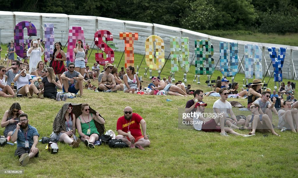 Revellers sit near a 'Glastonbury' sign after arriving to attend the Glastonbury Festival of Music and Performing Arts on Worthy Farm near the...