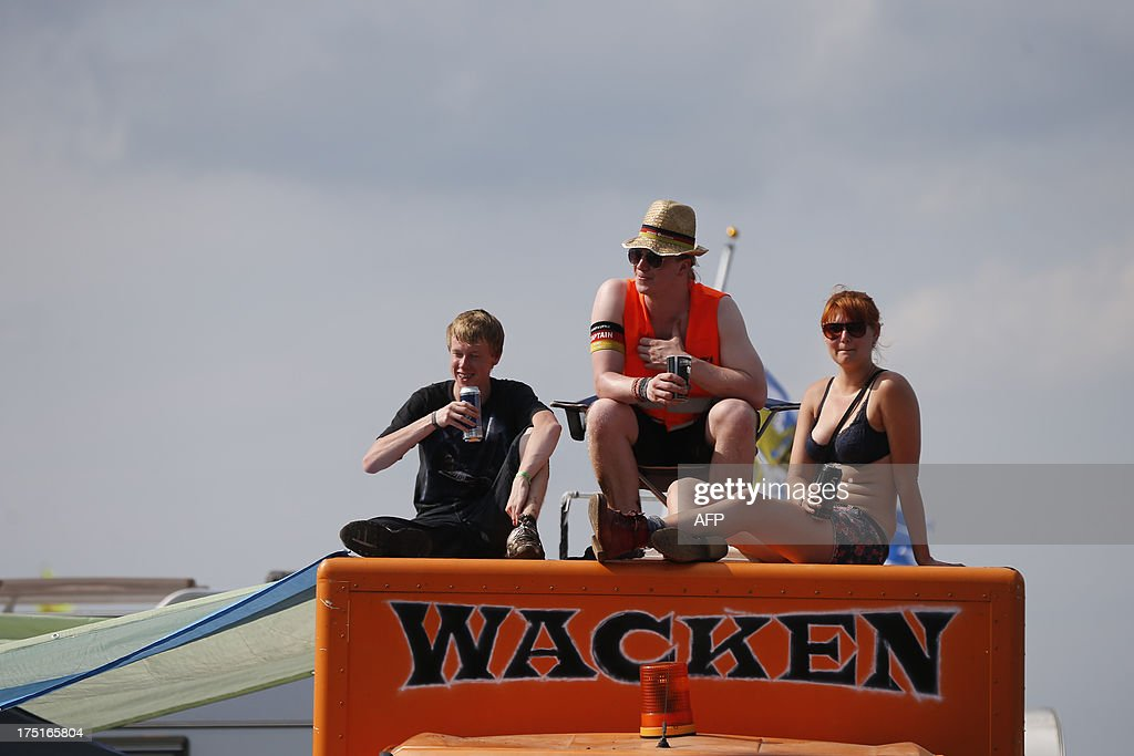 Revellers sit on their truck painted with the Wacken logo during the 24th heavy metal Wacken Open Air (WOA) Festival 2013 in Wacken, northern Germany on August 1, 2013. With some 80,000 festival visitors it attracts all kinds of metal music fans, such as fans of black metal, death metal, power metal, thrash metal, gothic metal, folk metal and even metalcore, nu metal and hard rock from around the world.