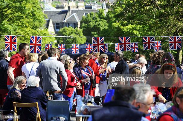 Revellers sit under decorations with Britain's Union flags during a street party to celebrate the Queen's Diamond Jubilee in Edinburgh on June 3 2012...