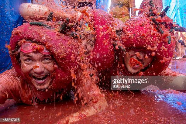 Revellers slide around in tomato pulp during the annual 'tomatina' festivities in the village of Bunol near Valencia on August 26 2015 Some 22000...