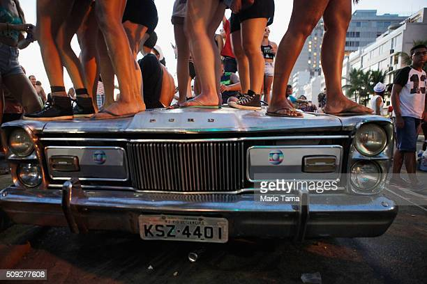 Revellers stand and dance atop a party vehicle during Carnival celebrations at the Banda de Ipanema 'bloco' or street parade on February 9 2016 in...