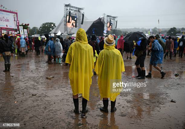 Revellers stand in the rain on the first official date of the Glastonbury Festival of Music and Performing Arts on Worthy Farm near the village of...