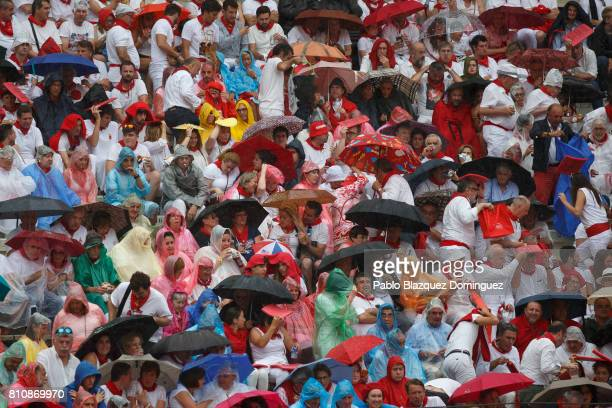 Revellers take cover from the rain as they watch a bullfight with Jose Escolar Gil's fighting bulls on the third day of the San Fermin Running of the...