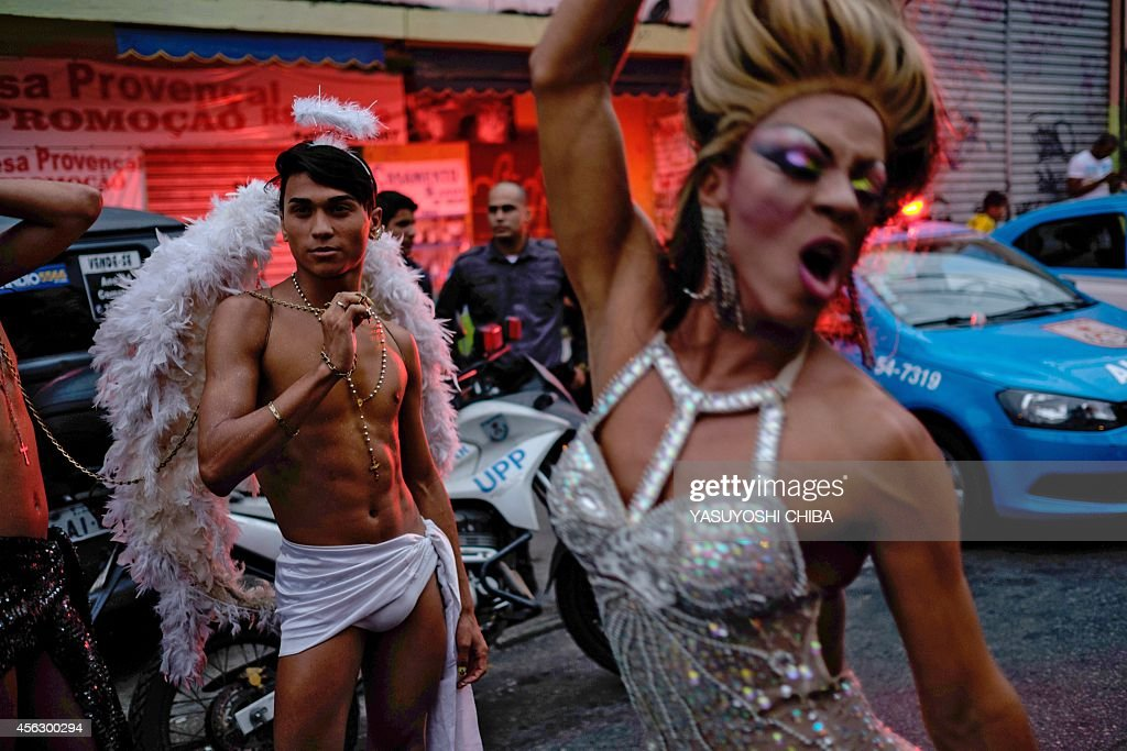 Revellers take part in the 2nd LGBT Pride Parade at Alemao favela in Rio de Janeiro, Brazil, on September 28, 2014. The annual parade aims for long-term actions to minimize prejudice and violences against the Lesbian, Gay, Bisexual, Transvestite and Transsexual community. AFP PHOTO / YASUYOSHI CHIBA