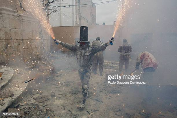 Revellers take part in the battle of 'Enfarinats' a flour fight in celebration of the Els Enfarinats festival on December 28 2015 in Ibi Spain...