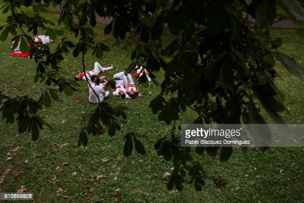 Revellers take rest in a park during the third day of the San Fermin Running of the Bulls festival on July 8 2017 in Pamplona Spain The annual Fiesta...