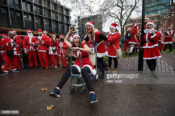 Revellers take turns to ride a luggage trolley as they take part in Santacon outside Euston Station on December 10 2016 in London England Santacon is...
