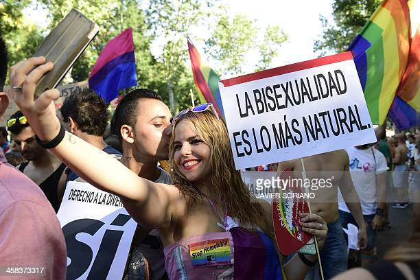 A revellers takes a selfie infront of a placard in favour of bisexuality during the Gay Pride Parade in Madrid on July 2 2016 / AFP / JAVIER SORIANO