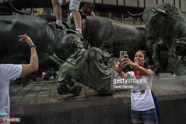 A revellers takes a 'selfie' next to a running of the bulls statue on the third day of the San Fermin Running of the Bulls festival on July 8 2015 in...