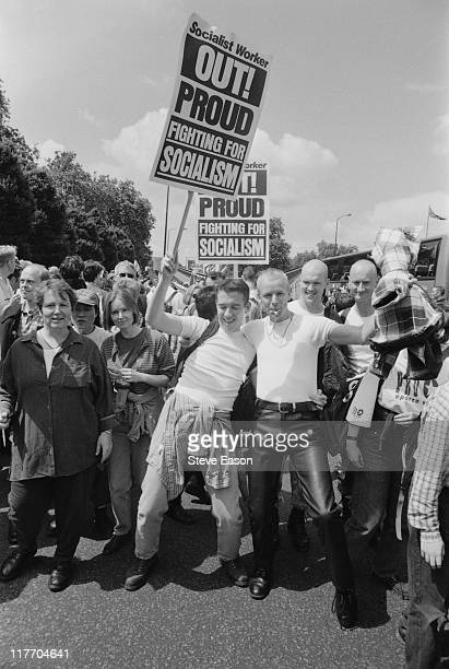 Revellers taking part in the Gay Pride parade carrying a placard that reads 'Out Proud Fighting for Socialism' in London England United Kingdom 6...