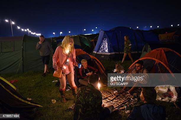Revellers talk by their tent at the Glastonbury Festival of Music and Performing Arts on Worthy Farm near the village of Pilton in Somerset South...