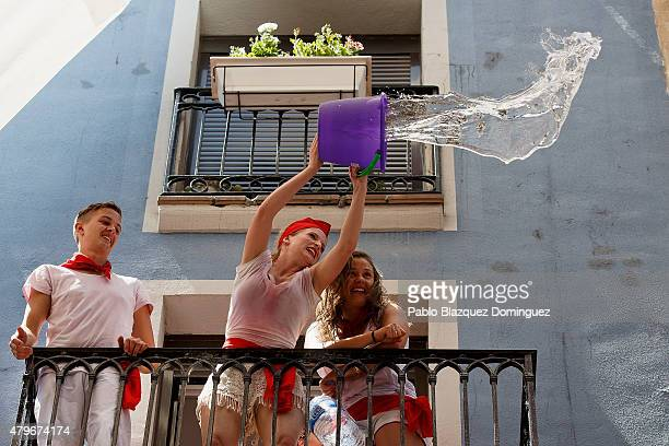 Revellers throw a bucket of water from a balcony to the crowd during the opening day or 'Chupinazo' of the San Fermin Running of the Bulls fiesta on...