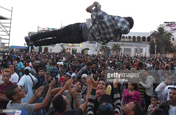 Revellers throw a youth in the air during the performamce of a group at the Gnaoua World Music Festival on June 13 2014 The annual festival provides...