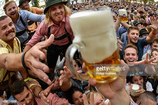 Revellers try to snatch free beer at the Hofbraeu tent on the opening day of the 2015 Oktoberfest on September 19 2015 in Munich Germany The 182nd...