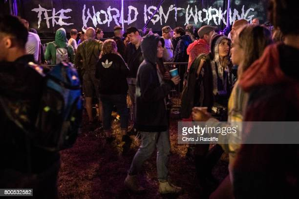 Revellers walk past a sign next to a bar that reads 'The world isn't working' in the Shangri La area at Glastonbury Festival Site on June 24 2017 in...