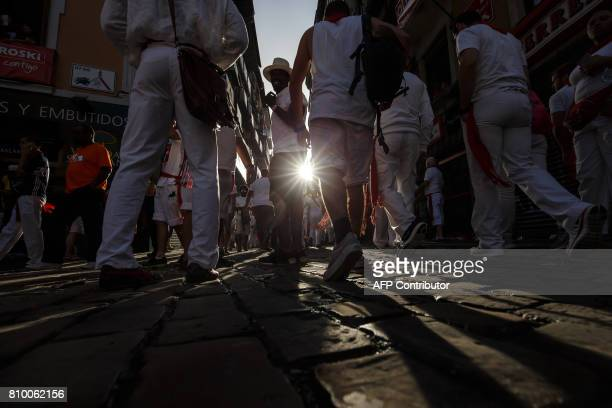 CORRECTION Revellers walk the street after the bull run on the first day of the San Fermin bull run festival in Pamplona northern Spain on July 7...